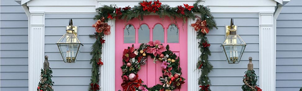 A front door decorated with wreaths and garlands